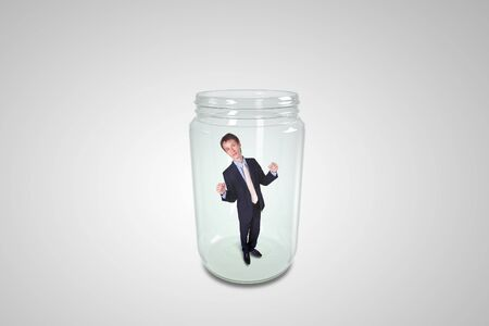 Businessman trapped inside a transparent glass jar Stock Photo - 14954579
