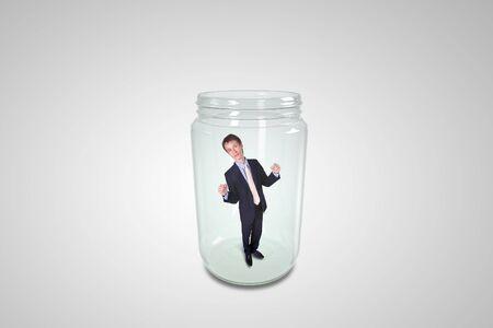 Businessman trapped inside a transparent glass jar photo