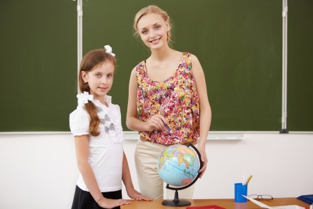 Young female teacher working with children at school photo