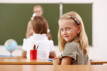 an elementary: Little girl sitting and studying at school class Stock Photo