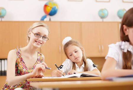 Young female teacher working with children at school Stock Photo - 14955111