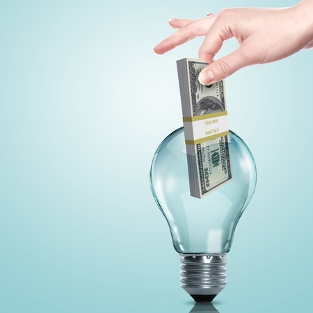 Hand and money inside an electric light bulb photo