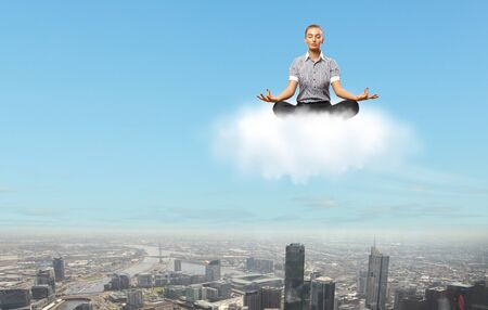 Businesswoman meditating sitting on the white cloud photo