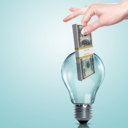 intellectual: Hand and money inside an electric light bulb Stock Photo