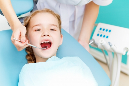 higiene bucal: Ni�a sentada en la oficina de dentistas