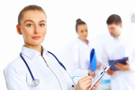 Young female doctor in white uniform with collegues on the background Stock Photo - 15006566