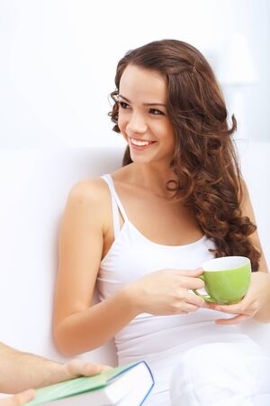Young pretty woman in white at home sitting on the sofa Stock Photo - 15006670