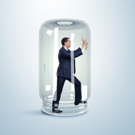 Businessman trapped inside a transparent glass jar photo