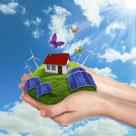 medio ambiente: Manos que sostienen una tierra verde con batareis solares Foto de archivo
