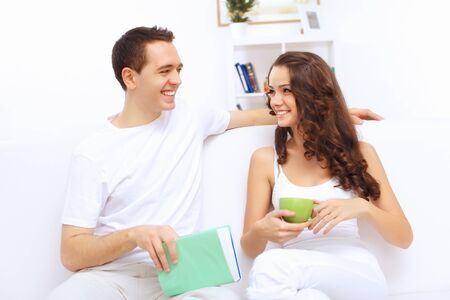 hone: Young happy couple at hone together sitting and talking