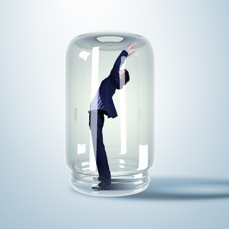 Businessman trapped inside a transparent glass jar Stock Photo - 15106857