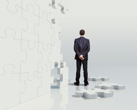business metaphor: Businessman with a puzzle pieces on the background