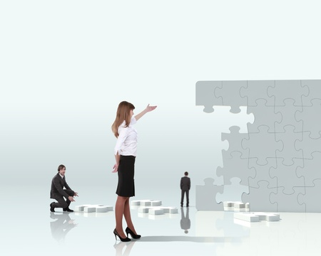 communication metaphor: Businesswoman with a puzzle pieces on the background Stock Photo