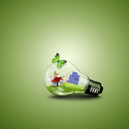 Electric light bulb and house inside it as symbol of green energy photo