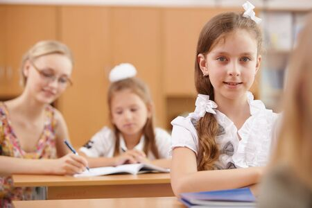 Little girl sitting and studying at school class photo