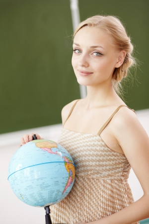 Young female teacher holding a globe at school Stock Photo - 15224196