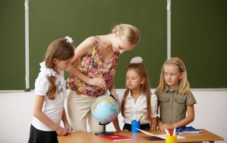 femme professeur: Jeune enseignante travaillant avec les enfants � l'�cole