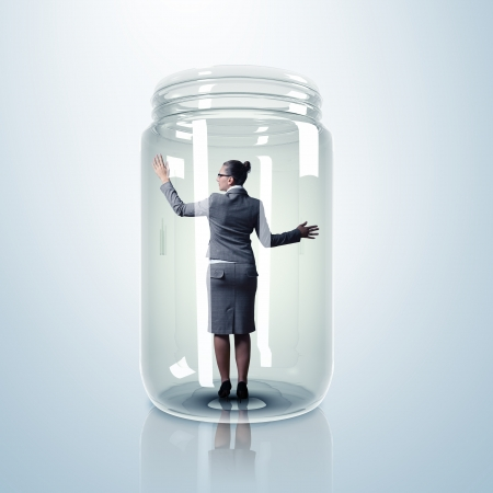 Businesswoman trapped inside a transparent glass jar photo