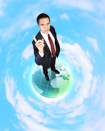 Planet earth against sky background and businessman standing on top of it photo