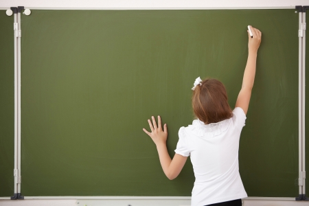Scoolgirl standing in class near a green blackboard photo