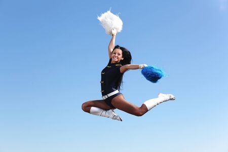 Young cheerleader in green costume jumping against blue sky Stock Photo - 15455712