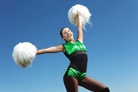 Young cheerleader in green costume jumping against blue sky Stock Photo - 15464280