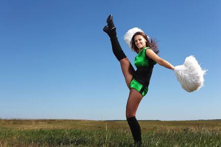 Young cheerleader in green costume jumping against blue sky Stock Photo - 15538128