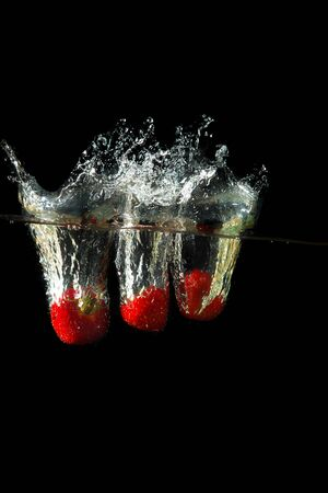 Colored red paprika in water splashes on black background Stock Photo - 15539318