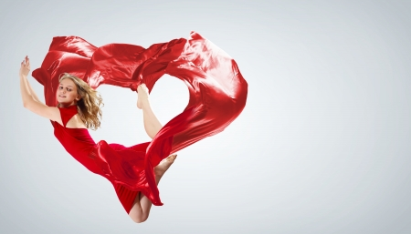Young woman dancing with red fabric in studio and heart symbol Stock Photo - 15539231
