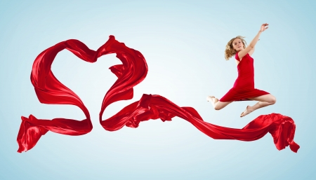 Young woman dancing with red fabric in studio and heart symbol Stock Photo - 15539229