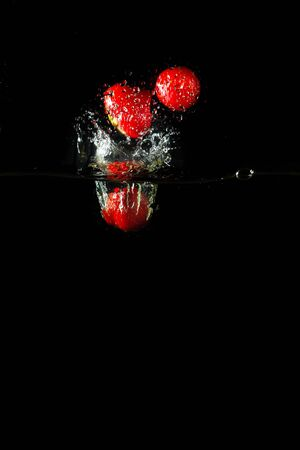 Colored red paprika in water splashes on black background Stock Photo - 15539179