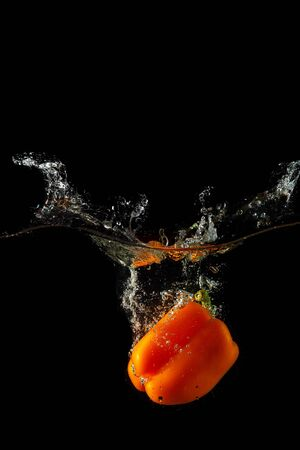 Colored orange paprika in water splashes on black background Stock Photo - 15539298