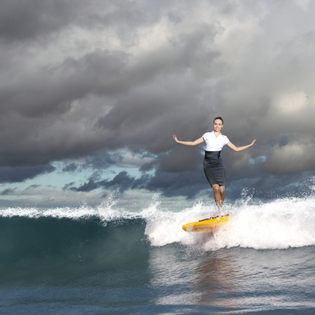 Image of young business person surfing on the waves of the ocean photo