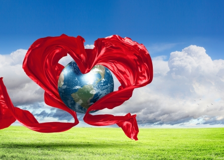 environmental protection: World within the heart symbol on blue sky background Elements of this image furnished by NASA  Stock Photo