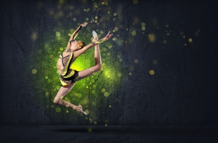 Young cute woman in gymnast suit show athletic skill on black background Stock Photo - 15539525