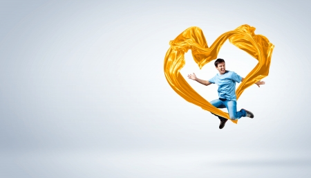 Young man dancing with yellow fabric over white background Stock Photo - 15539182