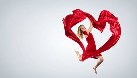 Young woman dancing with red fabric in studio and heart symbol Stock Photo - 15539226