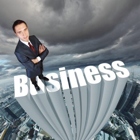 Businessman in suit standing on the word Business photo