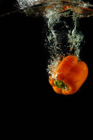 Colored orange paprika in water splashes on black background Stock Photo - 15539355