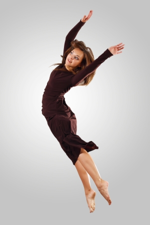 Young female dancer jumping against white background Stock Photo - 15539210