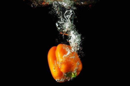 Colored orange paprika in water splashes on black background Stock Photo - 15539309