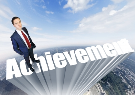 resourcefulness: Businessman in suit standing on the word Achievement Stock Photo