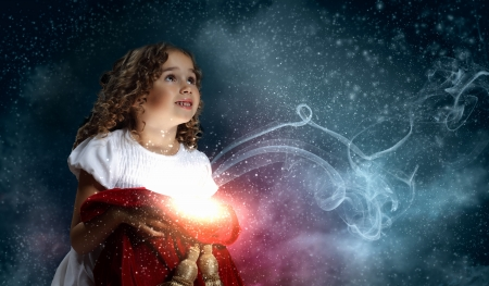 A cute young girl holding a christmas gift, dark background with christmas light bokeh photo