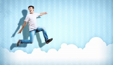 pretty modern slim hip-hop style man jumping dancing on a colour background photo