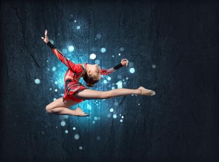 gymnastics: Mujer joven linda en traje de gimnasta mostrar habilidad atl�tica sobre fondo negro Foto de archivo