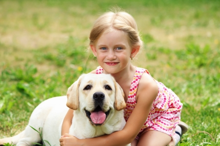pretty little girl: A little blond girl with her pet dog outdooors in park
