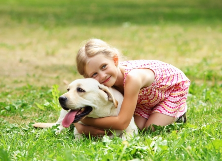 endear: A little blond girl with her pet dog outdooors in park
