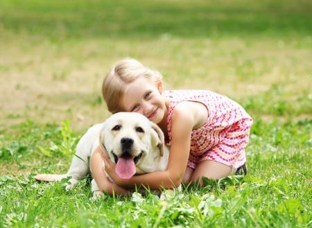 perros jugando: Una ni�a rubia con sus outdooors perro de animal dom�stico en el parque Foto de archivo
