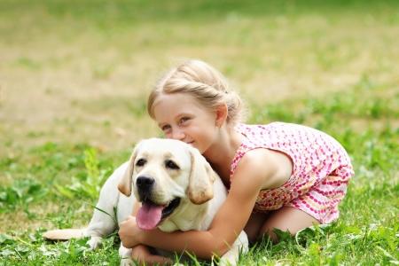 Een klein blond meisje met haar huisdier hond outdooors in park