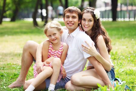 atcamera: Young Family Outdoors on the grass in Park in summer Stock Photo